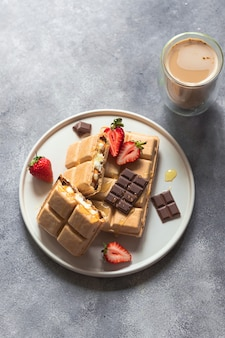 Wafel z lodami, miodem, truskawką, czekoladą. słodki deser widok z góry