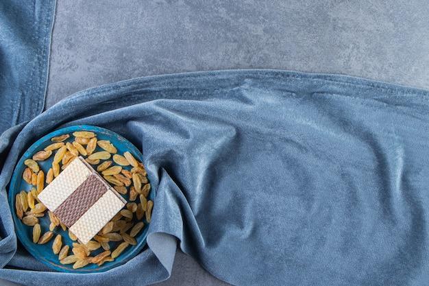 Wafel z rodzynkami na drewnianym talerzu na kawałku tkaniny, na marmurowym tle.