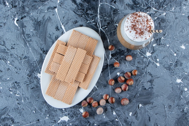 Wafelek paluszki z orzechami makadamia i szklanka smacznej gorącej kawy.