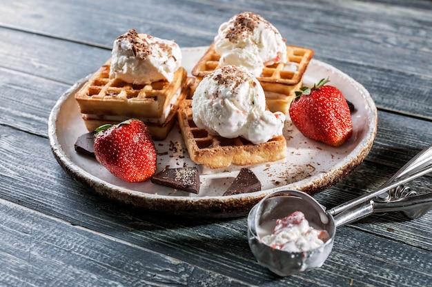 Wafle belgijskie z lodami waniliowymi, świeżymi truskawkami i czekoladą. pyszne śniadanie.