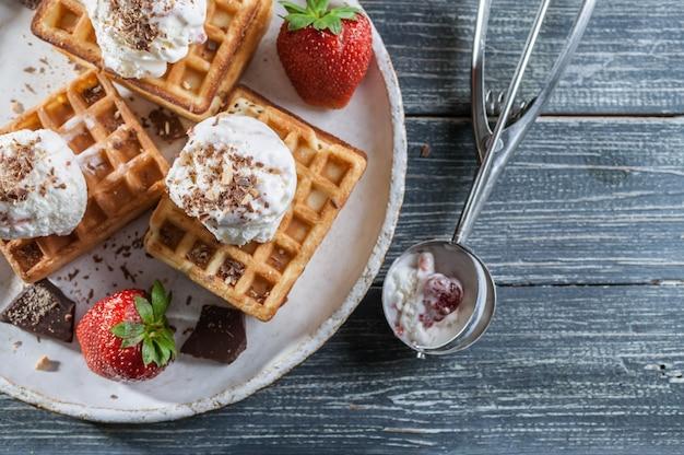 Wafle belgijskie z lodami waniliowymi, świeżymi truskawkami i czekoladą.