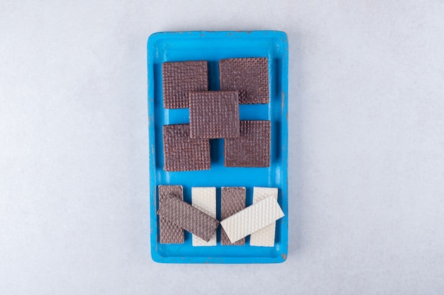 Wafle czekoladowe na drewnianym talerzu na marmurowym stole.