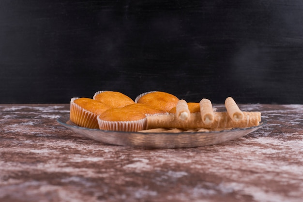 Wafle i babeczki w szklanym talerzu na marmurze na czarnej ścianie