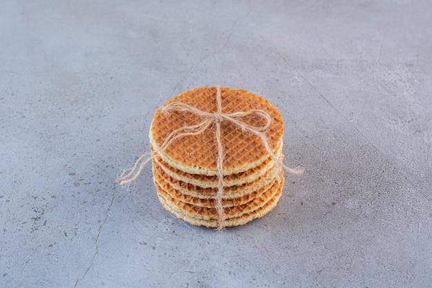 Wafle karmelowe związane kokardą z juty na białym tle na kamiennej powierzchni