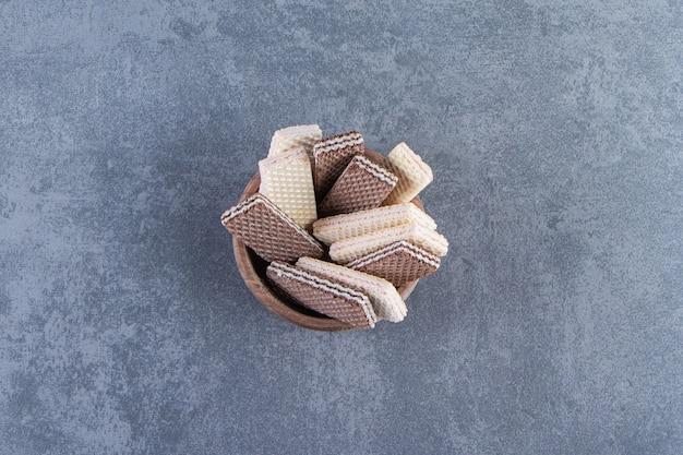 Wafle mleczne i czekoladowe w misce na marmurowej powierzchni