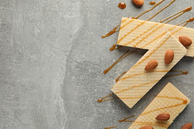 Wafle, polewy karmelowe i migdałów na szarym tle, miejsca na tekst
