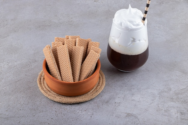 Wafle w misce z shake mleka na szarym tle.