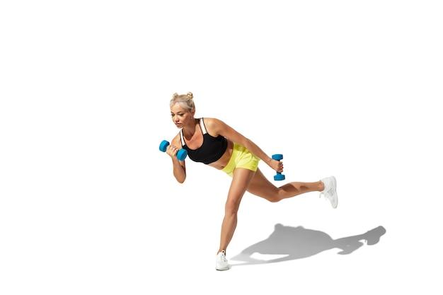 Wagi. piękna młoda lekkoatletka praktykujących na tle białego studia, portret z cieniem. model o sportowym kroju w ruchu i akcji. kulturystyka, zdrowy styl życia, koncepcja stylu.