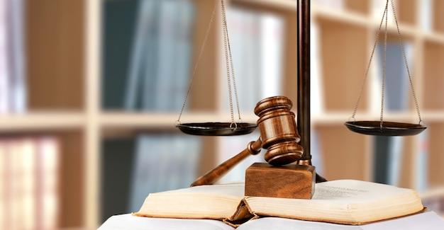 Wagi sprawiedliwości i książka i drewniany młotek na stole. koncepcja sprawiedliwości