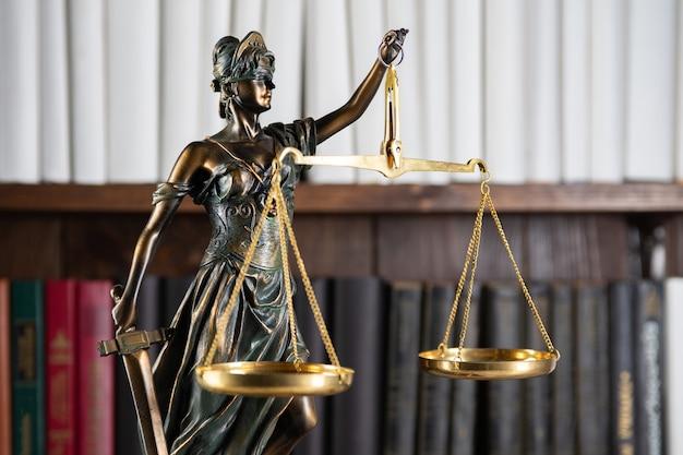 Wagi sprawiedliwości, lady justice, koncepcja biblioteki prawa, książki prawa w tle.
