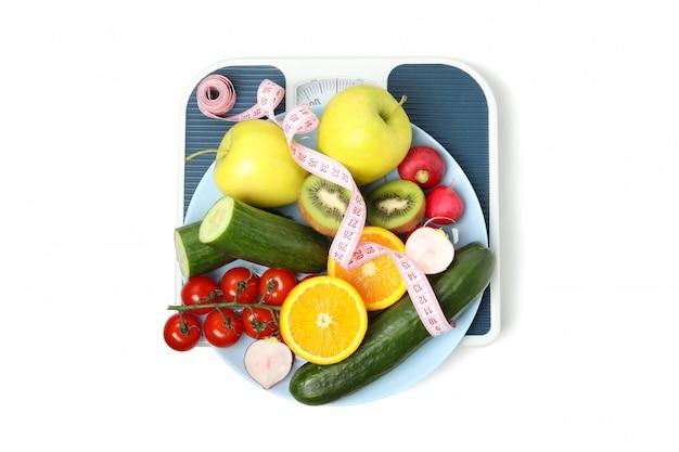 Wagi, taśma pomiarowa i wegetariańskie jedzenie na białym tle