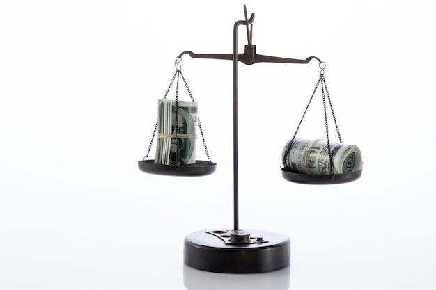 Wagi z gotówką na białym tle na białej powierzchni - koncepcja korupcji