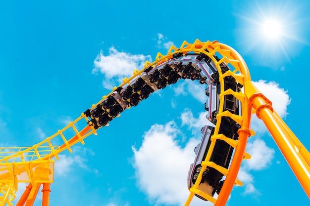 Wagon kolejowy rollercoaster bez ludzi testujących tor wysoko do nieba toczyć się i skręcać, aby uzyskać ekscytującą zabawę ludzi w parku rozrywki podczas pandemii koronawirusa (covid-19)