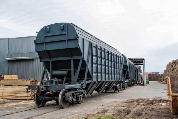 Wagony towarowe kolejowe w obszarze magazynu portowego czekają na rozładunek towarów.
