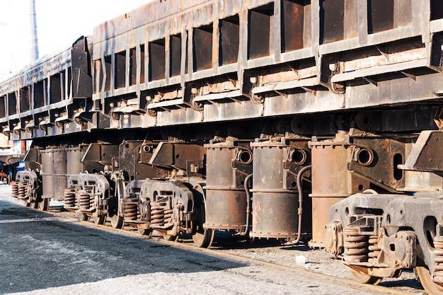Wagony towarowe na stacji kolejowej. koła i wózek kołowy z trzema osiami