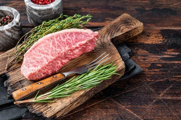 Wagyu a5 surowy rumsz lub stek z polędwicy wołowej, mięso wołowe kobe na desce rzeźniczej. ciemne drewniane tło. widok z góry. skopiuj miejsce.