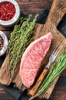 Wagyu a5 surowy rumsz lub stek z polędwicy wołowej, mięso wołowe kobe na desce rzeźniczej. ciemne drewniane tło. widok z góry.