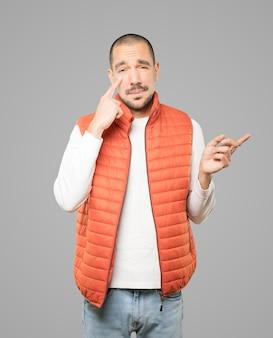 Wahający młody człowiek gestem ostrożności z ręką wskazującą na oko