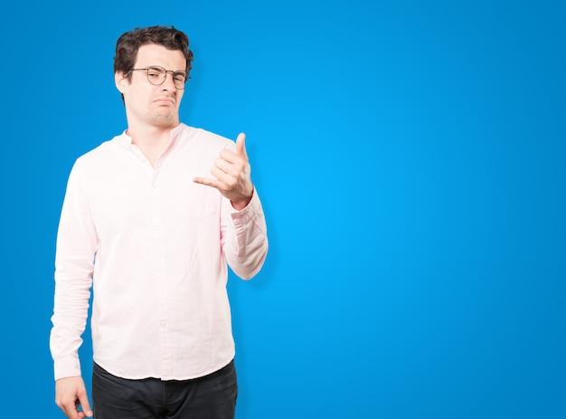 Wahający młody człowiek robi gest wołania ręką