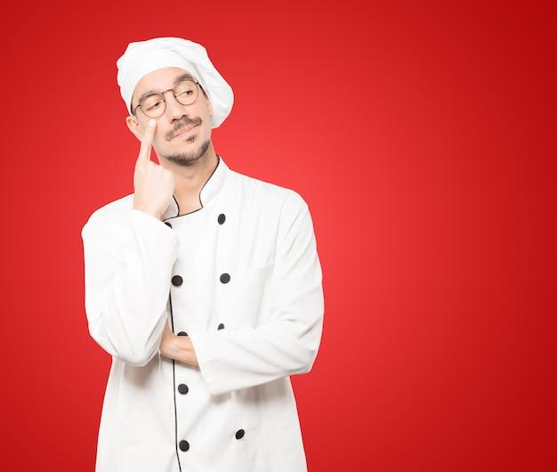 Wahający młody szef kuchni gestem ostrożności z ręką wskazującą na oko