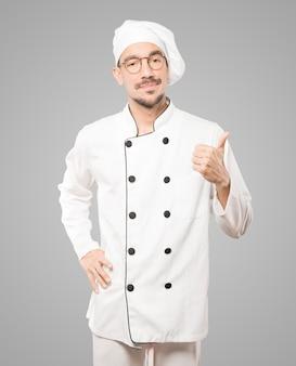 Wahający młody szef kuchni gestykuluje, że wszystko w porządku
