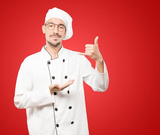 Wahający młody szef kuchni robi gest wołania ręką