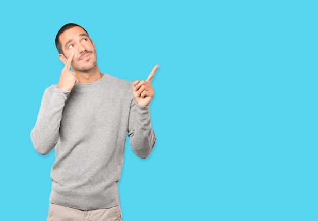 Wahający się młody człowiek robiący gest uważności, z ręką wskazującą na oko