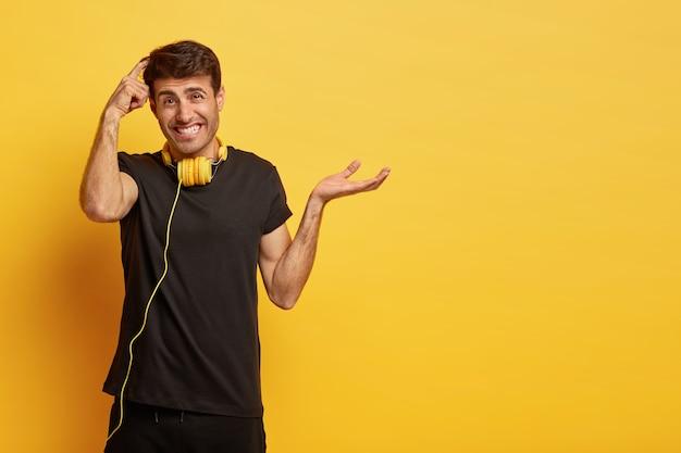Wahający się nieświadomy mężczyzna drapie się po głowie, podejmuje trudną decyzję, unosi dłoń z wahaniem, nosi zwykłą czarną koszulkę, słuchawki na szyi do słuchania muzyki