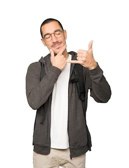 Wahający się student wykonujący gest wołania ręką