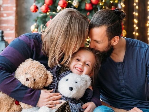 Wakacje dla całej rodziny. kochający rodzice całują swoją uroczą córeczkę. dziewczyna uśmiechnięta, siedząca szczęśliwa ze swoimi misiami.