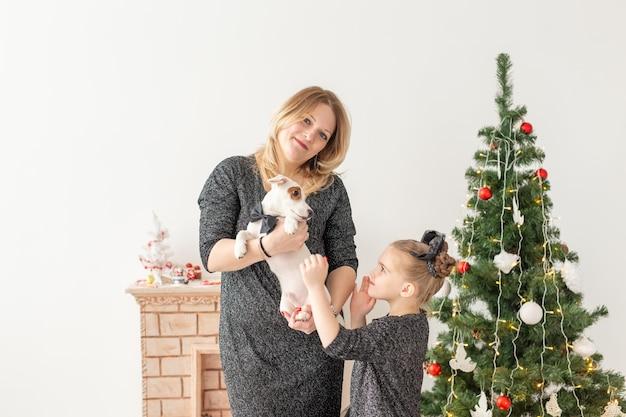 Wakacje i koncepcja zwierzaka - matka i córka bawi się z psem jack russell terrier przed choinką w domu.
