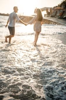 Wakacje i podróże. sexy kobieta i mężczyzna w wodzie morskiej o zachodzie słońca. kochająca para relaksuje się na plaży o wschodzie słońca. kocham związek pary cieszącej się letnim dniem razem