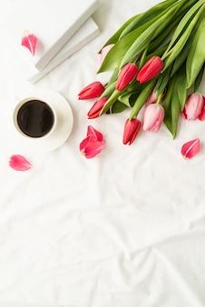 Wakacje i świętowanie. widok z góry na różowe tulipany, filiżankę kawy i książki na białym łóżku, leżał płasko