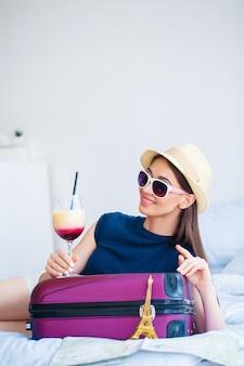 Wakacje. kobieta, która przygotowuje się do odpoczynku. młoda piękna dziewczyna siedzi na łóżku i trzyma w rękach koktajl. portret kobiety uśmiechnięta. szczęśliwa dziewczyna jedzie na wakacje