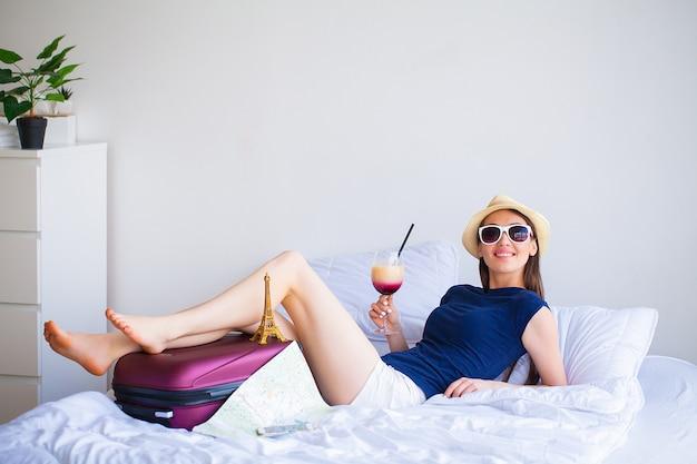 Wakacje. kobieta, która przygotowuje się do odpoczynku. młoda piękna dziewczyna siedzi na łóżku. portret kobiety uśmiechnięta. szczęśliwa dziewczyna jedzie na wakacje