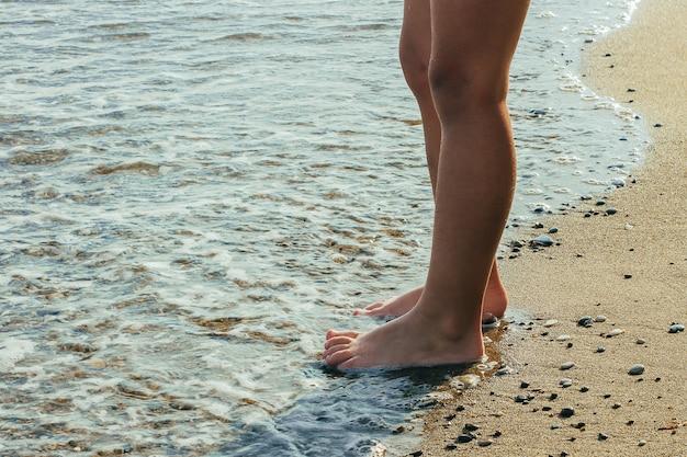 Wakacje. koncepcja wakacje. mały chłopiec stojący na plaży w wodzie. bose stopy.