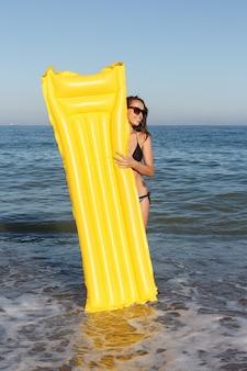 Wakacje, kurort, turystyka koncepcja - kobieta pływająca z nadmuchiwanym pączkiem na plaży w letni słoneczny dzień