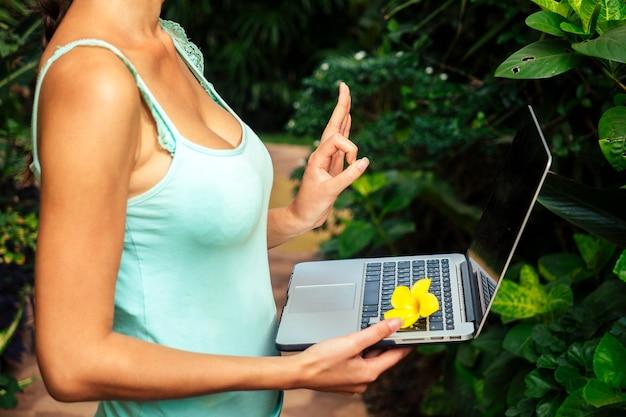 Wakacje kwiatowe lato młoda kobieta freelancer medytuje wokół laptopa