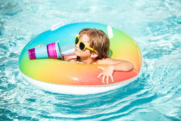 Wakacje letnie. dziecko pić koktajl w basenie. dziecko w aquaparku, wakacje letnie.