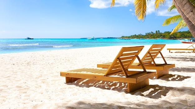 Wakacje letnie - słoneczny tropikalny raj na plaży z białym piaskiem, palmami i leżakami