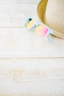 Wakacje letnie wakacje koncepcja tło, kapelusz, okulary przeciwsłoneczne, białe drewniane tła