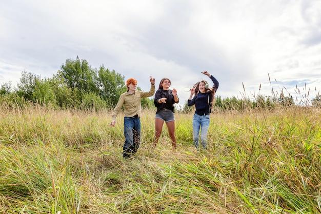Wakacje letnie wakacje szczęśliwych ludzi pojęcie. grupa trzech przyjaciół chłopca i dwóch dziewczyn tańczących i zabawy razem na świeżym powietrzu.