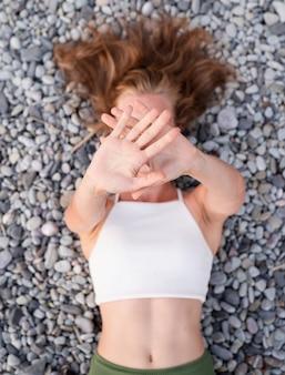 Wakacje letnie. widok z góry młoda uśmiechnięta kobieta w stroju kąpielowym, leżąc na kamiennej plaży, zakrywając twarz rękami. selektywne skupienie
