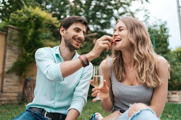 Wakacje, ludzie, romans, mężczyzna i kobieta karmią się truskawkami, pijąc musujące wino i ciesząc się razem w domu