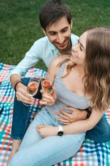 Wakacje, ludzie, romans, randki, para pije wino musujące podczas wspólnego spędzania czasu w domu na podwórku