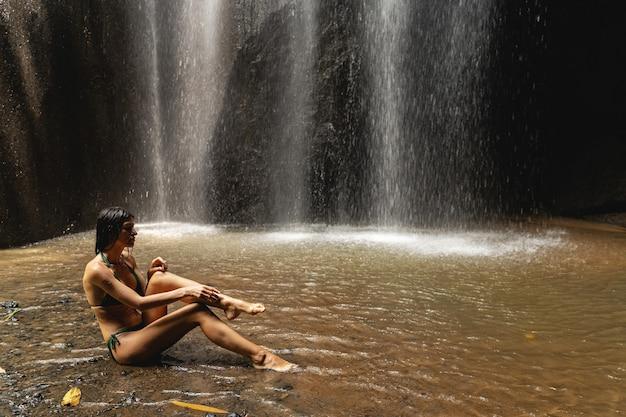 Wakacje moich marzeń. zadowolona brunetka siedzi przy wodospadzie i pokazuje swoją idealną figurę