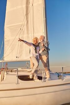 Wakacje na jachcie na całej długości szczęśliwej pary seniorów stojącej na boku żaglówki lub pokładu jachtu