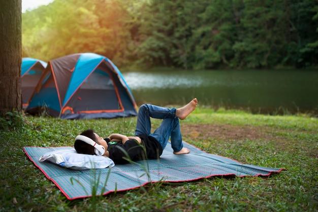 Wakacje na kempingu - młody chłopak odpoczywa na palecie w pobliżu namiotu w lesie