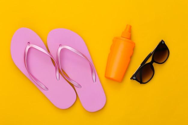 Wakacje na plaży. butelka z filtrem przeciwsłonecznym, okulary przeciwsłoneczne i klapki na żółto