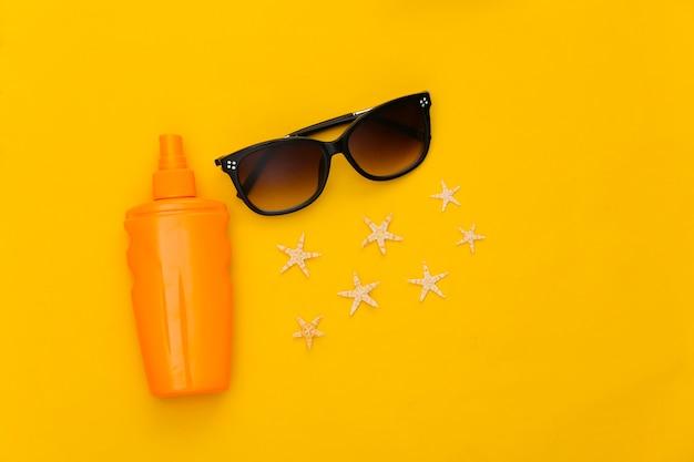Wakacje na plaży. butelka z filtrem przeciwsłonecznym, rozgwiazda i okulary przeciwsłoneczne na żółto